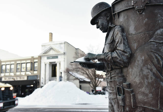 """A statue of a man on the courtsquare doesn't let a little snow on his work pad stop him from doing his job on Tuesday, Feb. 16. The worker is part of the """"Industry"""" statue on the north side of the courthouse. The plaque at the bottom of the statue reads """"Dedicated December 14, 2001. This sculpture celebrates industry in Sidney and Shelby County at the turn of the Millennium. One of four pieces representing important aspects of local life, it was donated by the Sidney/Shelby Public Art Foundation as part of the Millennium Monument project. It was created by sculptor George Danhires of Kent, Ohio. The Millennium Monument includes three additional sculptures placed on the Courthouse Square and related interactive historical kiosks accessible in City Hall and the Ross Historical Center. Commemorative donor and project participant plaques may be found in City Hall, as well as in the kiosk program."""""""