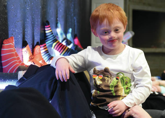 """Six-year-old Abel Saunders of Piqua is all smiles as the congregation of The Sanctuary Church shows their support for Abel and World Down Syndrome Awareness Day by showing their """"crazy socks"""" last week."""