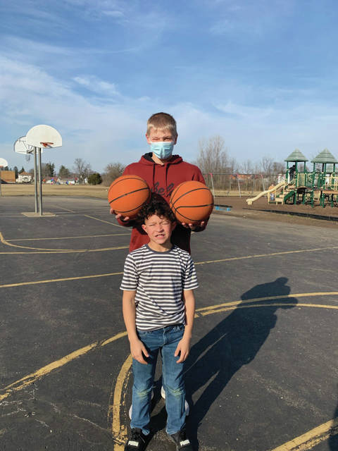 Big Buddy Mentor Damian Bruns, son of Jason and Jenny Bruns, of Fort Loramie, has fun with his Little Buddy mentee, Jayden Dotson, son of Kenya Steele, of Sidney, at a basketball court.