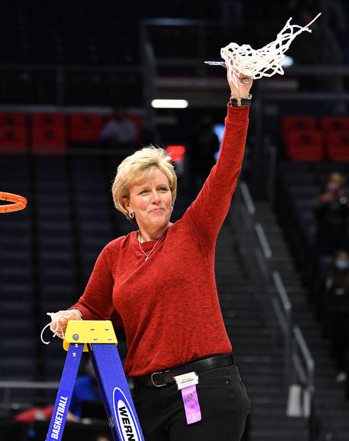 Fort Loramie coach Carla Siegel twirls the net after cutting it down following Fort Loramie's 60-26 victory over McDonald in the Division IV state championship game on Saturday at University of Dayton Arena.