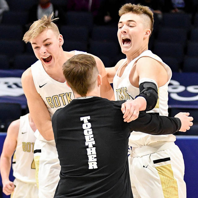 Botkins senior forward Denton Homan, right, and Cole Steinke celebrate with another player after defeating Richmond Heights 44-40 in a Division IV state semifinal on Friday at University of Dayton Arena. The Trojans didn't score for 10 minutes in the second half but finished with a 14-5 run in the last five minutes to earn the victory. They'll face Columbus Grove in the Div. IV state championship game on Sunday in Dayton.