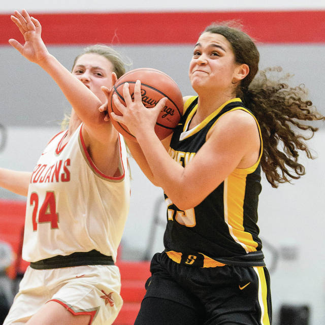 Sidney sophomore guard Allie Stockton drives down the lane with pressure from Troy's Elise McCann during the second half of a Miami Valley League game on Feb. 3 at the Trojan Activities Center in Troy. Stockton was named first team all-MVL for the second consecutive season.