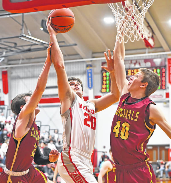 Columbus Grove's Ethan Halker shoots with pressure from New Bremen's Mitchell Hays, left, and Nathan Rindler during a Division IV regional on Friday at Van Wert High School.