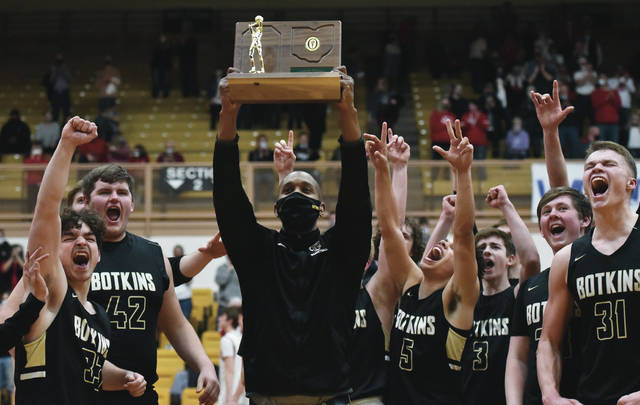 Botkins coach Sean Powell lifts up a Division IV regional championship trophy following a 42-40 win over Cedarville in a Division IV regional final on Friday at Vandalia-Butler's Student Activity Center. The Trojans will face Richmond Heights in a Division IV state semifinal this Friday at University of Dayton Arena.