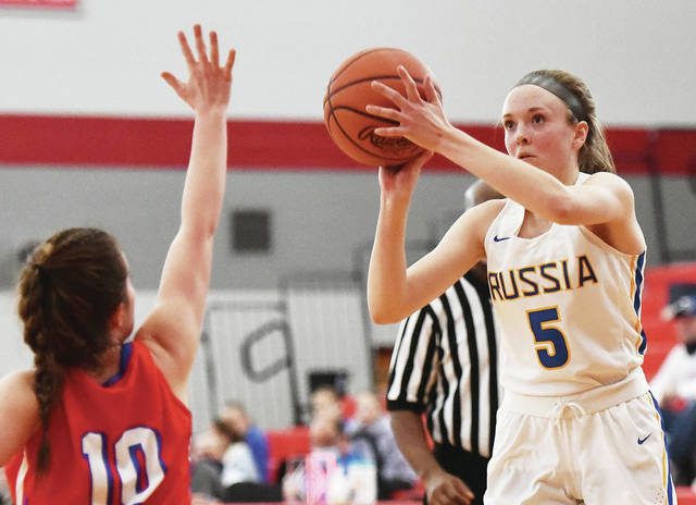 Russia's Cece Borchers shoots as Tri-Village's Dalanee Gray defends during a Division IV district final on Saturday at Troy High School's Trojan Activities Center. Borchers scored 11 points.