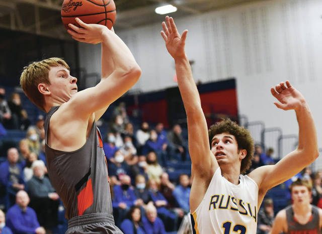 Jackson Center's Nolan Fark shoots with pressure Russia's Hayden Quinter during a Division IV district semifinal on Saturday at Garbry Gymnasium in Piqua. Fark scored 11 points to help the Tigers earn their third consecutive district final berth.