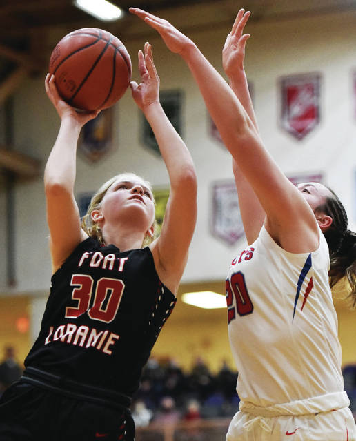 Fort Loramie senior forward Dana Rose shoots with pressure from Tri-Village's Meghan Downing during a Division IV regional final on Saturday at Vandalia-Butler's Student Activity Center.