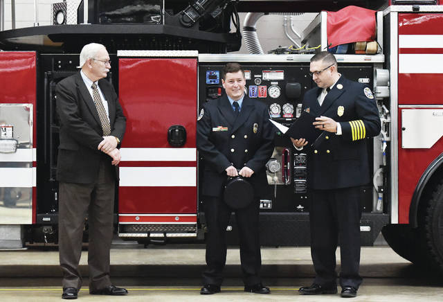 Chance Guisinger, center, is recognized as the 2019 Sidney firefighter of the year by Sidney Fire Chief Chad Hollinger, right, and Sidney Mayor Mike Barhorst during a ceremony at Sidney Fire Department Station 1 on Thursday, March 11. Guisinger was declared firefighter of the year in 2019 but due to COVID-19 a ceremony was never held for him.