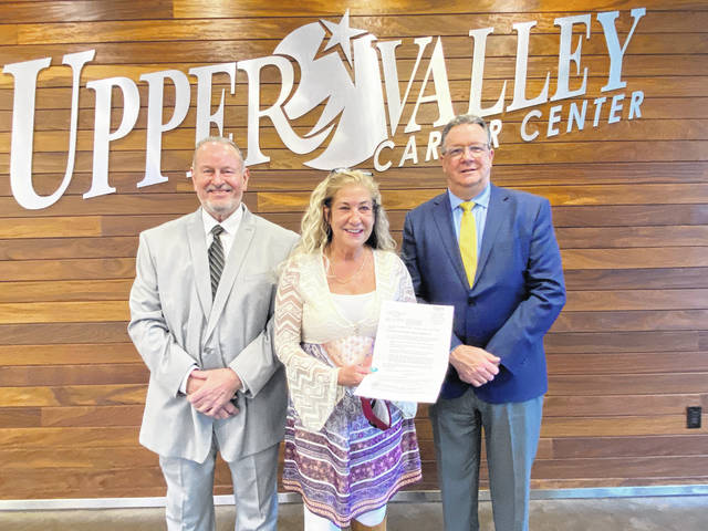 Mindy Hartzell, center, of Craft Interiors presents a residential building lot deed to Patrick Gibson, director of Business Operations for Upper Valley Career Center. Also in attendance from Craft Interiors is Terry Stamper, left.