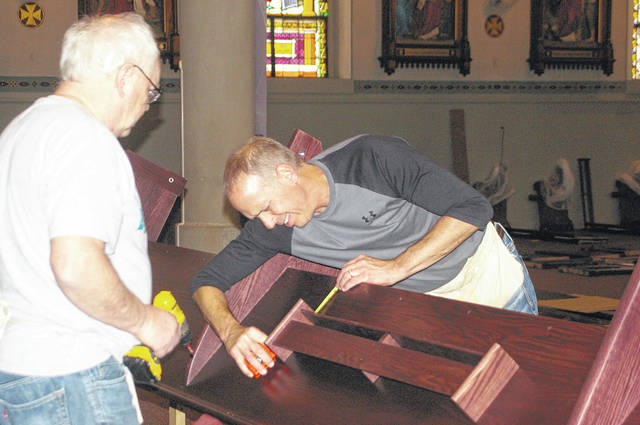 Ray Simonson, left, of Brookfield, Wisconsin, and Frank Boerger, of Fort Loramie, assemble pews Tuesday afternoon at St. Michael Church in Fort Loramie. Davis Furniture and Davis Manufacturing build church pews and worship seating that's installed throughout the United States and auditorium seating that's installed worldwide. Ed Davis, of Black River Falls, Wisconsin, and Simonson plan to finish installing some of the pews Thursday then will to go back to Wisconsin to get another load of pews to assemble. They will return to Fort Loramie on Monday and plan to have all the pews installed by Easter. Church services will resume at St. Michael Church on Saturday with a combination of pews and folding chairs for seating.