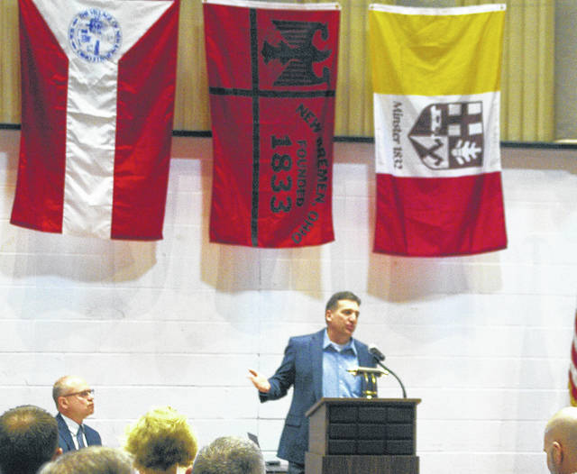 With the flags of New Knoxville, New Bremen and Minster behind him, New Knoxville Mayor Keith Leffel speaks during the Southwestern Auglaize County Chamber of Commerce's State of the Villages breakfast Thursday morning at the New Bremen American Legion.