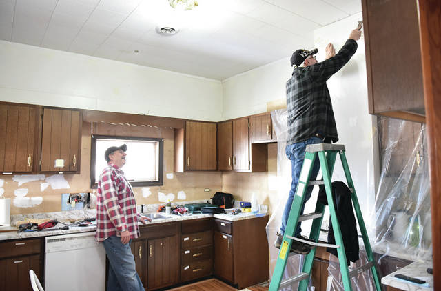 Cecil Steele, right, of Sidney, scrapes away paint from the wall of the upstairs kitchen at the Ross Historical Center on Wednesday, Feb. 24 as Richard Bailey, of Minster, watches. The kitchen will get new paint and new wallpaper.