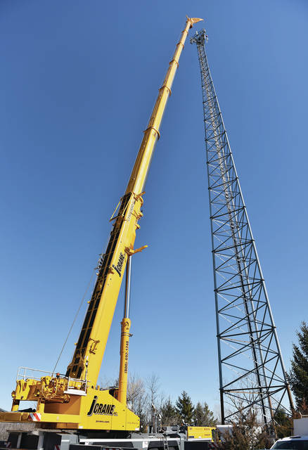 A crane lifts a part up to the top of a cell tower located behind the Sidney Electric Co. building on South Vandemark Road. The crane spent Tuesday, March 2, working on the tower.