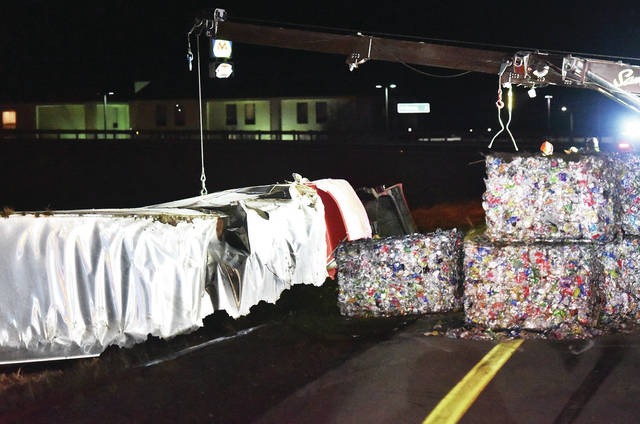 A semi trailer lies crumpled on the side of the South bound exit 90 ramp after flipping over while exiting. On the right are cubes of crushed aluminum cans that were removed from the crashed semi trailer. The Ohio State Highway Patrol responded to the crash which occurred around 6:30 p.m. on Thursday, March 4. The sharply curving exit ramp has become a common site for semi trailer crashes.