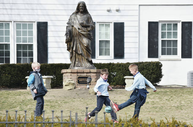 Holy Angels Catholic School students, left to right, Ayden Lundy, 7, Simon Goubeaux, 7, and Kamdyn Snow, 7, all of Sidney, play a game of soccer under a statue of Jesus during recess on Tuesday, March 9. Ayden is the son of Brian and Kris Lundy. Simon is the son of Kyle and Emily Goubeaux and Kamdyn is the son of Dustin and Molly Snow.