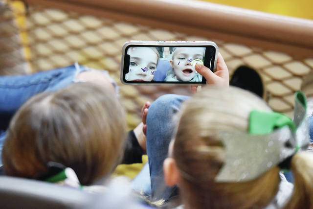 Digital butterflies land on the faces of best friends, Nora Steinke, left, 6, and Lenynn Billing, 6, both of Anna, as they play with a cell phone while they attended the Anna Rockets' basketball game against Taft in Vandalia on Wednesday, March 10. Nora is the daughter of Taylor and Julia Steinke. Lenynn is the daughter of Jess and Jessica Billing.