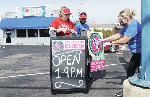 Five minutes before 1 p.m. on Friday, March 12 K&J's Ice Cream employees, left to right, Alayna Milks, of Piqua, and Aleyce Cunningham, help their boss Kim Curlis, both of Sidney, set-up a sign with their current hours. It was K&J's season opening. The ice cream shop will be open seven days a week.