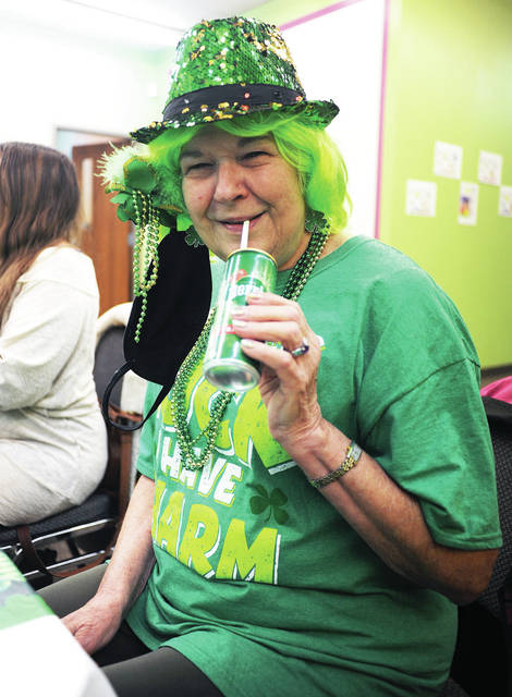 "Pam Pollard, of Sidney, drinks water during lunch with her Bible study group, ""Our Father's House"" at Russell Road Church on Tuesday, March 16. Group members dressed in St. Patrick's Day green for their meeting."