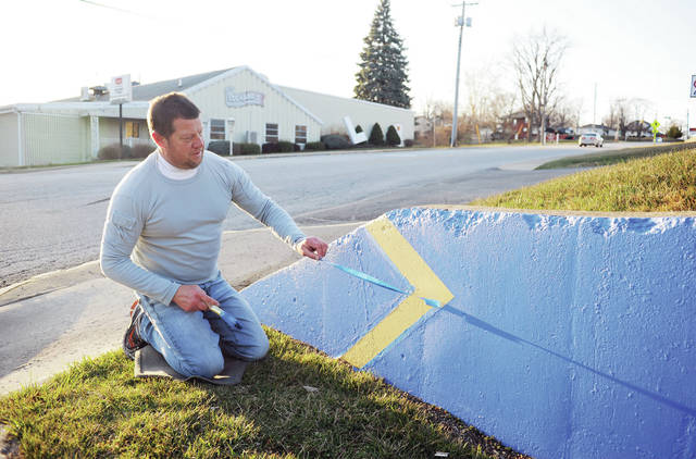 Legacy Auto Sales Owner David Frierott, of Sidney, pulls tape from the wall behind his car dealership as he applies some fresh paint to brighten it up on Friday, March 19. The business is located at 822 Wapakoneta Avenue.