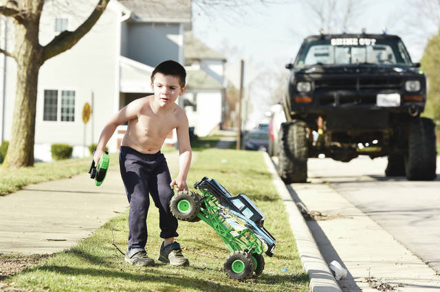 Lucis Fitzpatrick, 3, of Sidney, son of Leah Stone and Daniel Fitzpatrick, moves his monster truck from the street to a sidewalk. The truck was a Christmas present. Lucis was playing with his remote control truck along Oak Avenue on a sunny Monday, March 29.