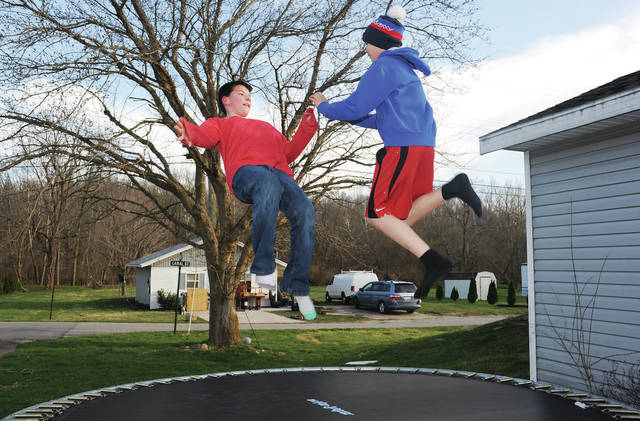 A.J. Howard, left, 11, and his friend Ronald Reeves, 11, both of Port Jefferson, bounce on the trampoline in A.J.'s yard in Port Jefferson, on Tuesday, March 30. The two often jump on the trampoline together. A.J. is the son of Maryann Howard and Jessy Howard. Ronald is the son of Travis and Hazel Reeves.