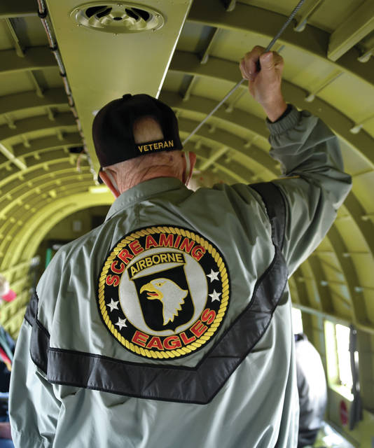 """Former U.S. Army 101st Airborne paratrooper Ron Tucker of Cincinnati grasps the """"hook-up"""" cable inside historic C-47 That's All Brother just as he did while a paratrooper in the famed 101st Airborne, and inside the same aircraft that some 16 paratroopers jumped behind German lines on June 6, 1944, over Normandy."""