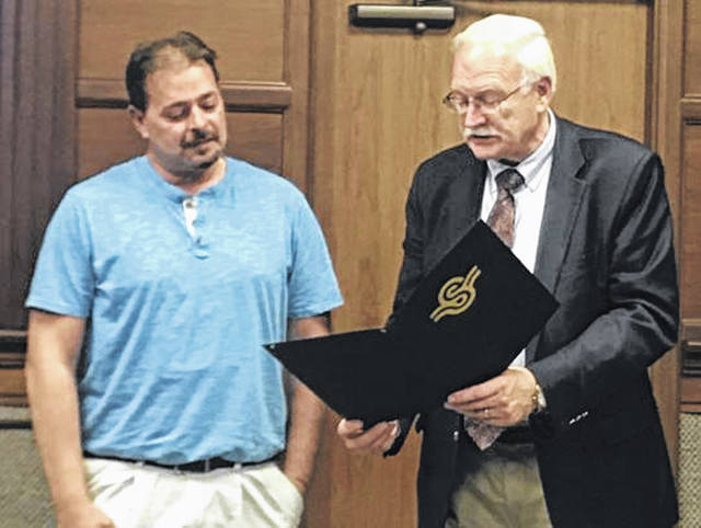 Brian Green, Sidney street manager/ISA certified arborist, left, receives Arbor Day proclamation from Mayor Mike Barhorst Monday evening at the Sidney City Council meeting.