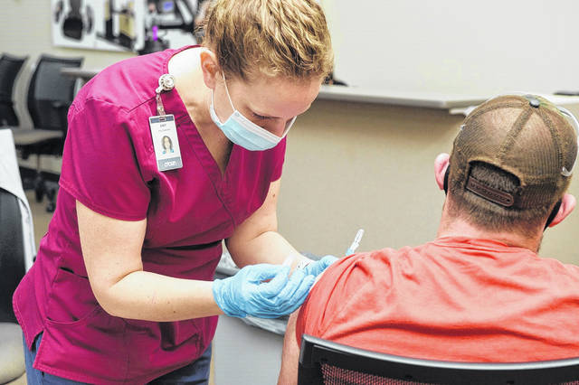 Crown held two COVID-19 vaccination clinics for its employees. Amy Bateman, of Celina, gives the vaccine shot to Devin Laemmle, of Van Wert.