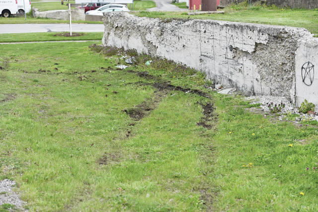 Tire tracks show where the SUV struck a concrete wall next to Lake Street.