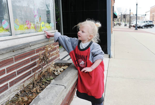 Riley Geise, 3, of Fort Loramie, finds a numbered Easter egg in the window of a shop in downtown Sidney on Wednesday, March 31. Riley was searching for the numbered eggs in the windows of downtown businesses with her brother, Connor Geise, 5, and their mother, Megan Geise. The eggs were part of the Downtown Sidney Easter Egg Hunt put on by Sidney Alive. Participants write down on a list the name of the store they found the numbered egg at. When all the eggs are found they turn the list into Sidney Alive to be part of a drawing to win a prize basket. Riley and Connor are also the children of Jason Geise.