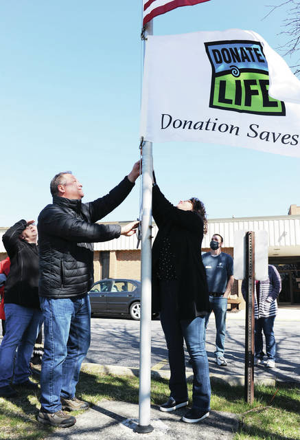 Tim Cantrell and Jodi Cantrell, both of Sidney, raise a Donate Life flag in front of the Sidney-Shelby County YMCA on Friday, April 2. Tim and Jodi raised the flag for Donate Life Awareness Month and in memory of Susan Cantrell who passed away in 2020 due to cancer, 10 years after receiving a liver transplant. Susan was Tim's wife and Jodi's sister. Watching the flag raising in the background are Bambi Wagner, far left, and YMCA Property Manager Ray Zachrich, both of Sidney.