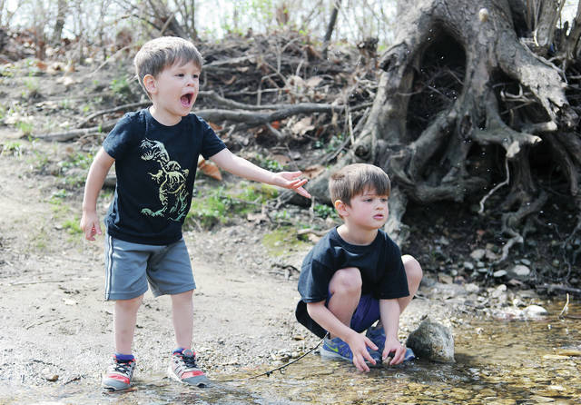 Matthew Wisniewski, left, 3, throws a rock into Tawawa Creek as his brother, Logan Wisniewski, 5, both of Sidney, watches in Tawawa Park on Tuesday, April 6. The brothers were exploring the park with their mother, Megan Wisniewski. They are also the children of Nathan Wisniewski.