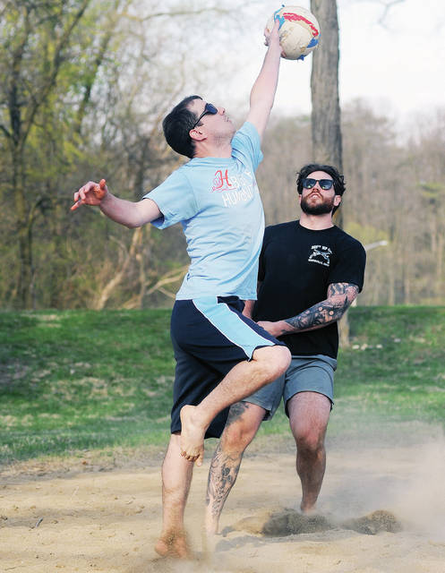 Adam D'Amico, left, of Sidney, stretches for the ball while his teammate, Vinny Anderson, of Kettering, backs him up during a game of volleyball at Blackston Picnic Grove, on Wednesday, April 7. The two men are part of a group of Emerson Climate Technologies employees who have been playing together for 10 years.