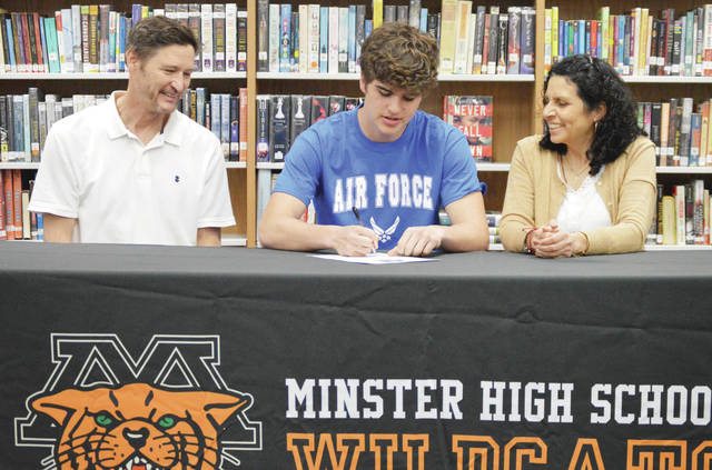 Minster High School senior Isaiah Slonkosky, center, 18, signs a form confirming his commitment to joining the U.S. Air Force Reserves. Watching him are his parents Ed, left, and Mary Lou Slonkosky, all of Minster. Slonkosky signed the form in the Minster High School media center on Thursday, April 8. Slonkosky was inspired by his three older brothers who have also joined the U.S. Air Force.