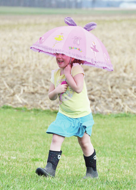 """Alana Garrett, 5, of Fort Loramie, daughter of Suzanne and Scott Garrett, sings """"Rain, rain, go away,"""" while walking in her backyard on Fort Loramie-Swanders Road on Thursday, April 8. Suzanne said her daughter had received the elaborately decorated umbrella a week ago and just wanted to test it out in the rain."""