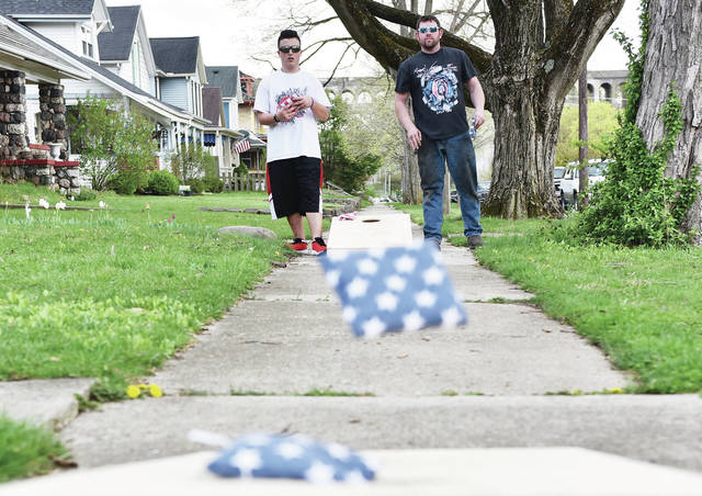 Steven Martin, left, 14, of Sidney, son of Erica and Steve Martin, plays a game of cornhole with Shane Miles, of Piqua, on the sidewalk next to South Main Avenue on Monday, April 12.