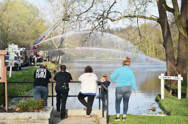 People watch as A Lockington firetruck, front to back, Sidney firetruck and Maplewood firetruck siphon water out of Tawawa Lake and spray it back in during a joint firefighter training exercise on Tuesday, April 13.