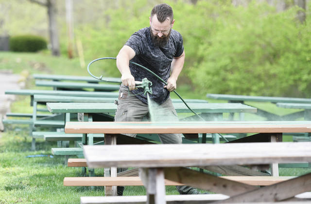 Realtor Josh Wolaver, of Sidney, sprays picnic tables with green paint at Tawawa Park on Friday, April 16. Wolaver was painting the picnic tables to help out Tawawa Park and to promote Bryce Realty. Wolaver said his co-worker Misty Ott came up with the suggestion and has also been helping paint the tables. They agreed to paint a total of 50 picnic tables.