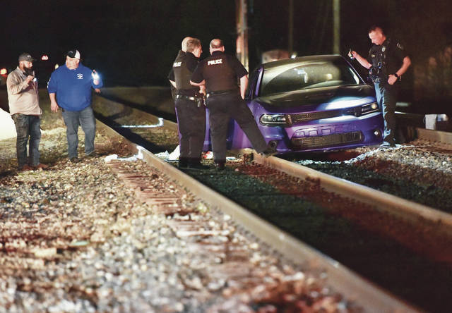 Botkins police officers investigate a car stuck on railroad tracks just north of where they intersect with West State Street in Botkins Saturday night, April 17. A search was held in Botkins which included the Shelby County Sheriff's Office and other local law enforcement.