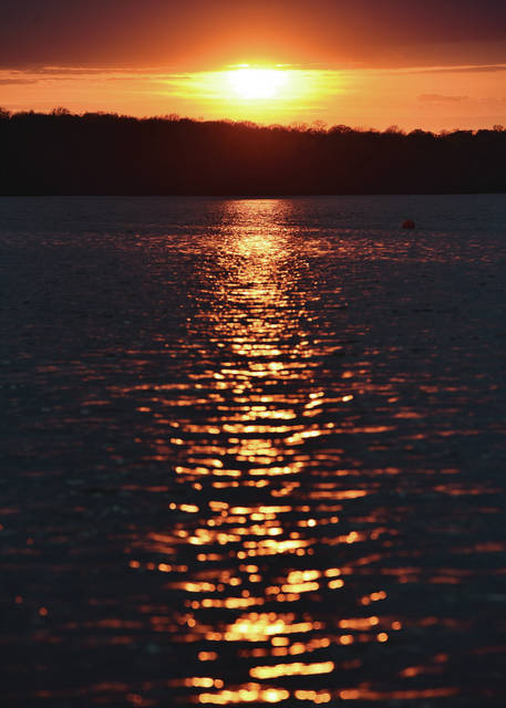 Sunlight glitters off of Kiser Lake as the sun sets on Monday, April 19. The lake had a handful of people fishing from the shore and a few kayakers on the water.