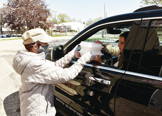 Kiwanis Club of Sidney member Linda Meininger, left, hands out pancake meals at the Shelby County Fairgrounds during the Kiwanis Club's Annual Pancake Day on Wednesday, April 21.