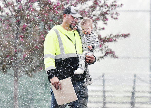 Ben Lengerich, gets caught in some sudden heavy snow at Custenborder Field with his son Camden Lengerich, 1, both of Sidney, on Wednesday, April 22 around 5 p.m. Lengerich was at Custenborder Field to pick up baseball uniforms for the T-ball team he will be coaching this year. The team's name is Roe Trucking. Camden is also the son of Heather Lengerich. The heavy snowfall was brief unlike the large amount of snow that fell the night before.