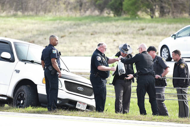 After a vehicle chase, Anna Police Chief Darrin Goudy, right, front, holds up a clear plastic bag filled with various objects towards Botkins Police Chief Wayne Thomas Glass Jr., in front of a Ford F150 in the median of I-75 just north of the Russell Road overpass. Also present was the Shelby Sheriff's Office, Sidney Police and the Ohio State Highway Patrol.