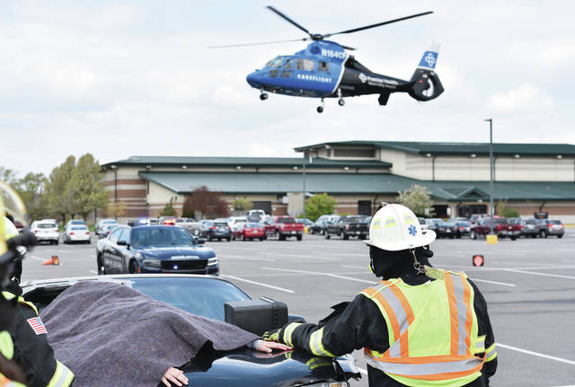 Vivian Niekamp, 17, of New Bremen, lies under a blanket while playing a dead body during a mock car crash behind the New Bremen High School on Thursday, April 22. Taking off with another victim of the crash is Careflight. New Bremen students watched the mock crash which included members of the New Bremen Fire Department, Police Department and New Bremen EMS. Niekamp is the daughter of Mandy and Nate Niekamp.
