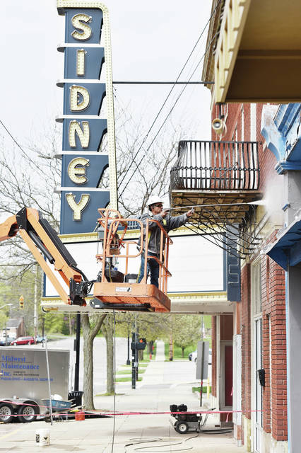 Eddie Rivera, of Piqua, pressure washes The Historic Sidney Theatre on Friday, April 23. Rivera has been cleaning the outside of the building and doing some restoration such as recaulking the windows. Rivera plans on applying a water sealant to the outside of the building sometime this weekend.
