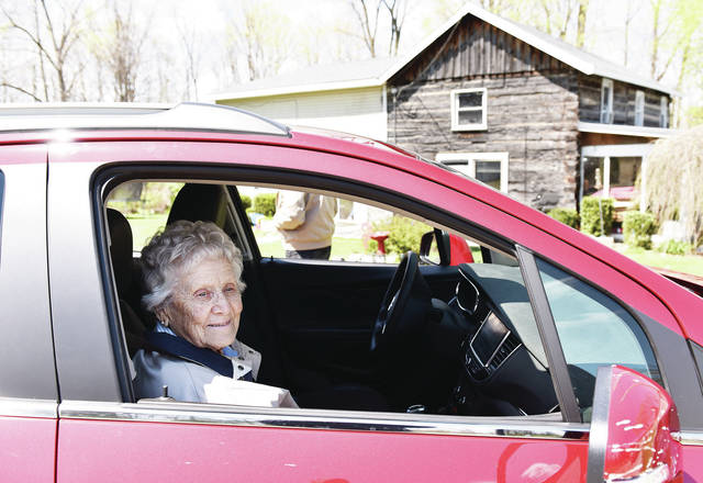 Barbara Allen Ditmer sits in front of her great-great-grandpa, George Frasier's house in Sidney, on Wednesday, April 21. Barb has carried on her families farming legacy through 4-H.