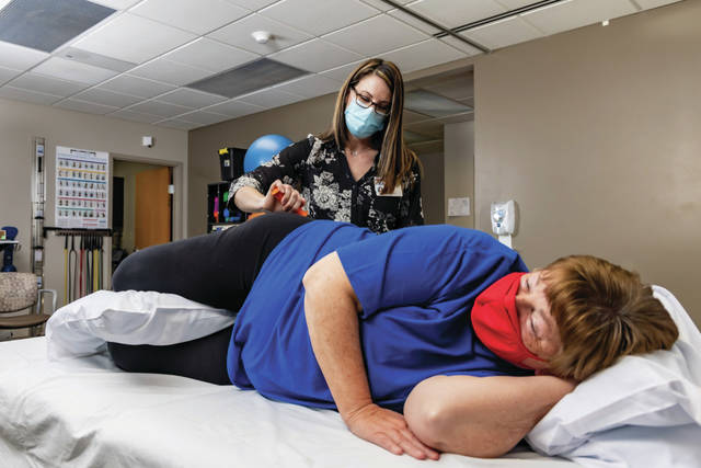 Physical therapist Megan Burns, standing, works with Judy Ross at the UVMC Sidney Center.