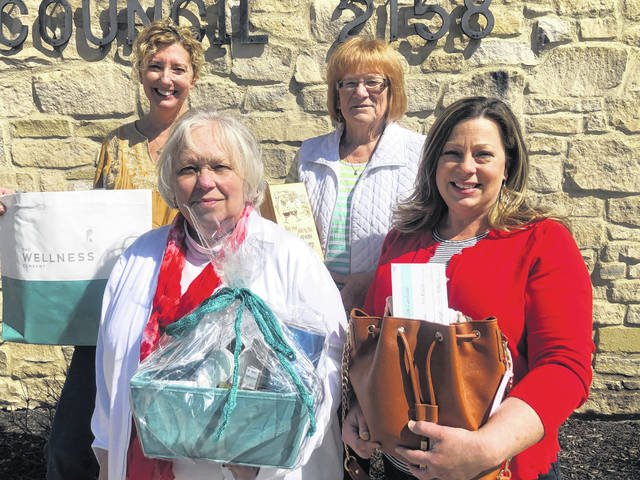 Carly Morsey and Connie Seger, back row, and Sue Doenges and Sara Suchland, front row, show a few of the door prizes that will be given way at the bridal show.