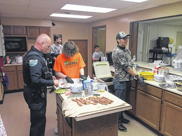 """Community Resource Officer Bryce Stewart, left, Jake Cromes, center in orange, 16, the son of Jennifer Kelly, Elijah Wade, 16, right, the son of Timothy and Trinity Wade, Josh Scott, 14, the son of Sylvia Watson and Josh Scott, back left, and Jericho Hale, 12, son of Stephanie and Johnathan Hale, back right, work together to prepare for a meal they are cooking on Thursday, April 1. A group of Sidney students are participating in the Sidney Police Department's new weekly """"Cookin with Cops"""" program."""