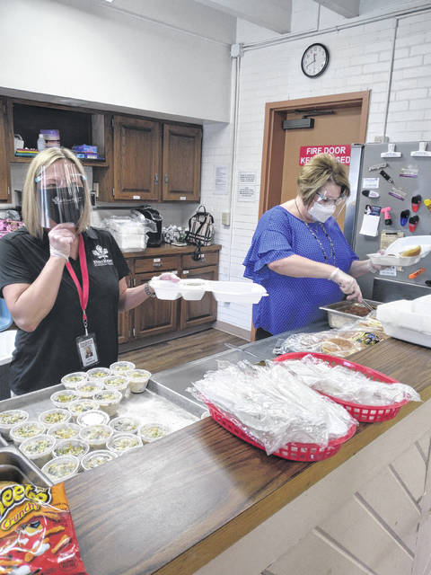 Kristi Miller, Buckeye Home Heath, and Michelle Stollmer, The Landings of Sidney, serve lunch to members of the Senior Center of Sidney and Shelby County Wednesday in observance of World Health Day. They also provided free blood pressure checks.